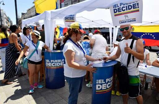 A Venezuelan resident (R) in Madrid thumbs up as he votes at a polling station during a symbolic plebiscite on president Maduro's project of a future constituent assembly, called by the Venezuelan opposition and held at the Puerta del Sol in Madrid on July 16, 2017. Hundreds of Venezuelans queued in the blazing heat in Madrid today to vote in an opposition-organised vote to measure public support in Venezuela for President Nicolas Maduro's plan to rewrite the constitution.    / AFP PHOTO / GERARD JULIEN