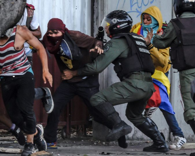 Members of Venezuela's National Guard chase anti-government activists as protests build ahead of a controversial vote to elect an assembly to rewrite the constitution