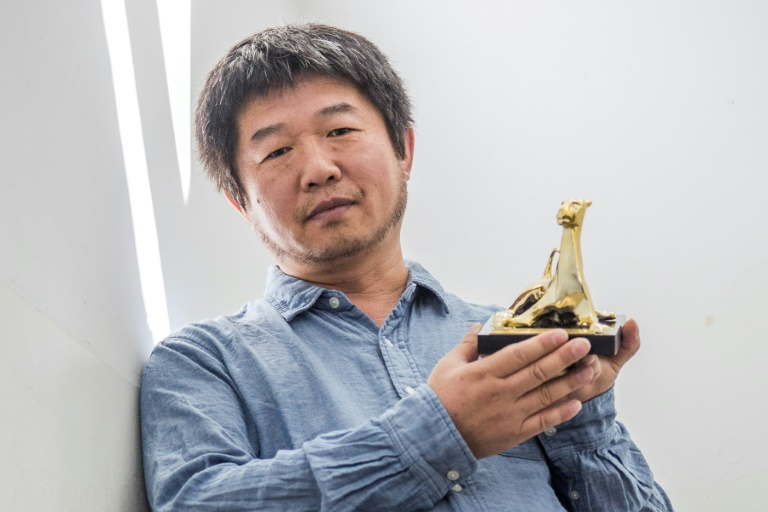 """Chinese director Wang Bing poses with the Golden Leopard (Pardo d'oro) trophy he wobn for his documentarty """"Mrs. Fang"""", in a picture released on August 12, 2017 by the Locarno International Film Festival"""