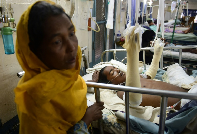 Rohingya Muslim refugee Rashida Begum (L) stands next to her son Azizul Hoque, 15, as he is treated after being injured by a landmine while crossing from Myanmar to Bangladesh, at a hospital in Cox's Bazar