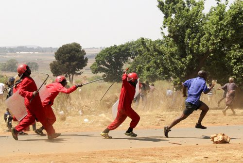 A red Ant security guard chase after community members at Vlakfontein extension 4, Johannesburg, 22 September 2017. Red Ants demolished hundreds of shacks in the area and it is alleged that 6 people died. Picture: Cebile Ntuli