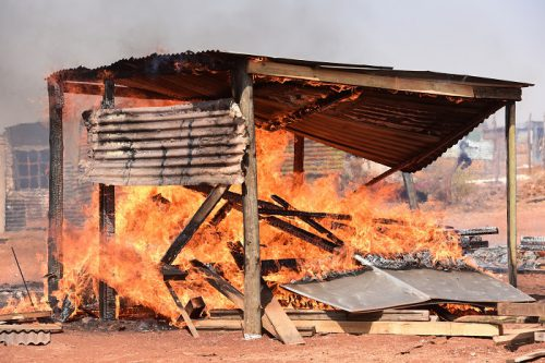 A shack on fire during the battle between community members and Red Ants at Vlakfontein extension 4, Johannesburg, 22 September 2017. Picture: Nigel Sibanda