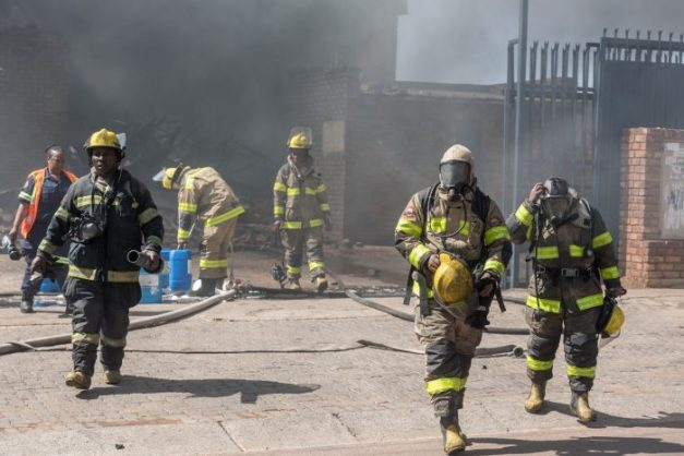 Firefighters leave a building warehouse during a fire at a paint store on Soutter Street in Pretoria West on 16 October 2017. The fire was compounded by flammable paints and thinners in the building. Picture: Yeshiel Panchia