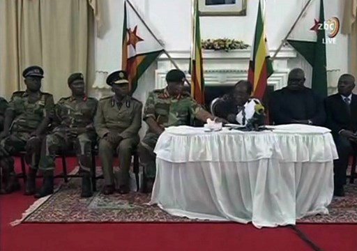 """A video grab made on November 19, 2017 from footage of the broadcast of Zimbabwe Broadcasting corporation (ZBC) shows Zimbabwe's President Robert Mugabe (C) delivering a speech in Harare, following a meeting with army chiefs who have seized power in Zimbabwe. Zimbabwean President Robert Mugabe, in a much-expected TV address, stressed he was still in power after his authoritarian 37-year reign was rocked by a military takeover. Many Zimbabweans expected Mugabe to resign after the army seized power last week. But Mugabe delivered his speech alongside the uniformed generals who were behind the military intervention. In his address, Mugabe made no reference to the clamour for him to resign.   / AFP PHOTO / ZBC / STR / XGTY / RESTRICTED TO EDITORIAL USE - MANDATORY CREDIT """"AFP PHOTO / ZBC"""" - NO MARKETING NO ADVERTISING CAMPAIGNS - DISTRIBUTED AS A SERVICE TO CLIENTS"""