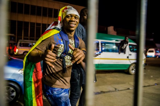A man wearing the national flag celebrates in the streets after the resignation of Zimbabwe's president Robert Mugabe on November 21, 2017 in Harare. Car horns blared and cheering crowds raced through the streets of the Zimbabwean capital Harare as news spread that President Robert Mugabe, 93, had resigned after 37 years in power. / AFP PHOTO / Jekesai NJIKIZANA