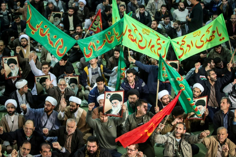 Iranians chant slogans as they march in support of the regime near the Imam Khomeini grand mosque in Tehran on December 30, 2017