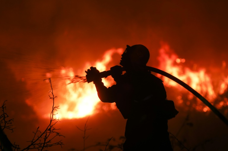 A firefighter battles a wildfire as it burns along a hillside near homes in Santa Paula, California that has forced thousands to flee the area