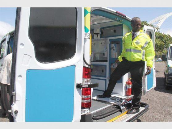 KZN health MEC Dr Sibongiseni Dhlomo standing next to an ambulance.