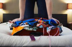 Woman Kneeling on Bulging Suitcase --- Image by © moodboard/Corbis