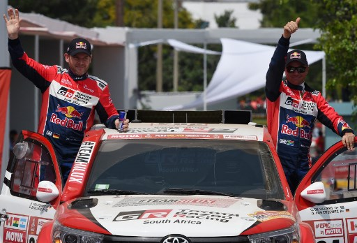Toyota's driver Giniel De Villiers (R) of South Africa and his co-driver Dirk Von Zitzewitz of Germany wave from the podium, during the start of the 2018 Dakar Rally, ahead of the rally's Lima-Pisco Stage 1, in Lima on January 6, 2018. The 40th edition of the Dakar Rally will take competitors through Peru, Bolivia and Argentina until January 20. / AFP PHOTO / CRIS BOURONCLE