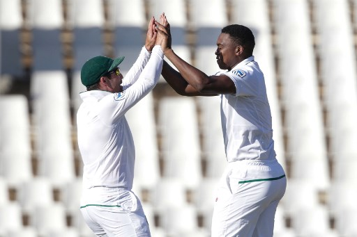 South African bowler Lungi Ngidi (R) and fielder Dean Elgar (L) celebrate the dismissal of Indian batsman Lokesh Rahul (not in picture) during the fourth day of the second Test cricket match between South Africa and India at Supersport cricket ground on January 16, 2018 in Centurion. / AFP PHOTO / GIANLUIGI GUERCIA