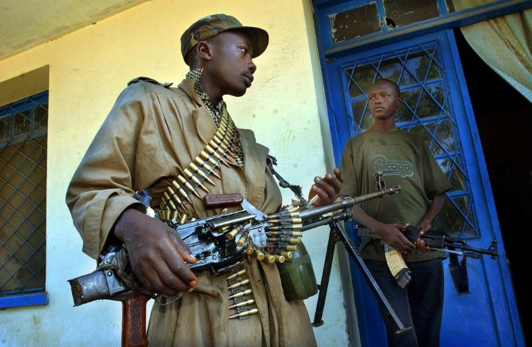 Heavily armed militiamen guard a party office in Bunia, the main city in the volatile Ituri province