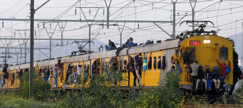 An overloaded train travels to Khayelitsha in Cape Town with some passengers sitting on the roof. Picture: Bheki Radebe