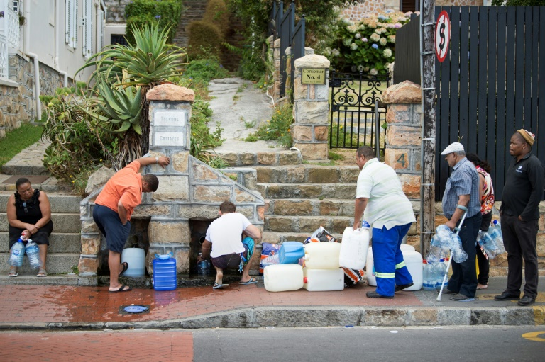 Residents from the Cape Town area collect drinking water from pipes, as a three-year-long drought grips the city