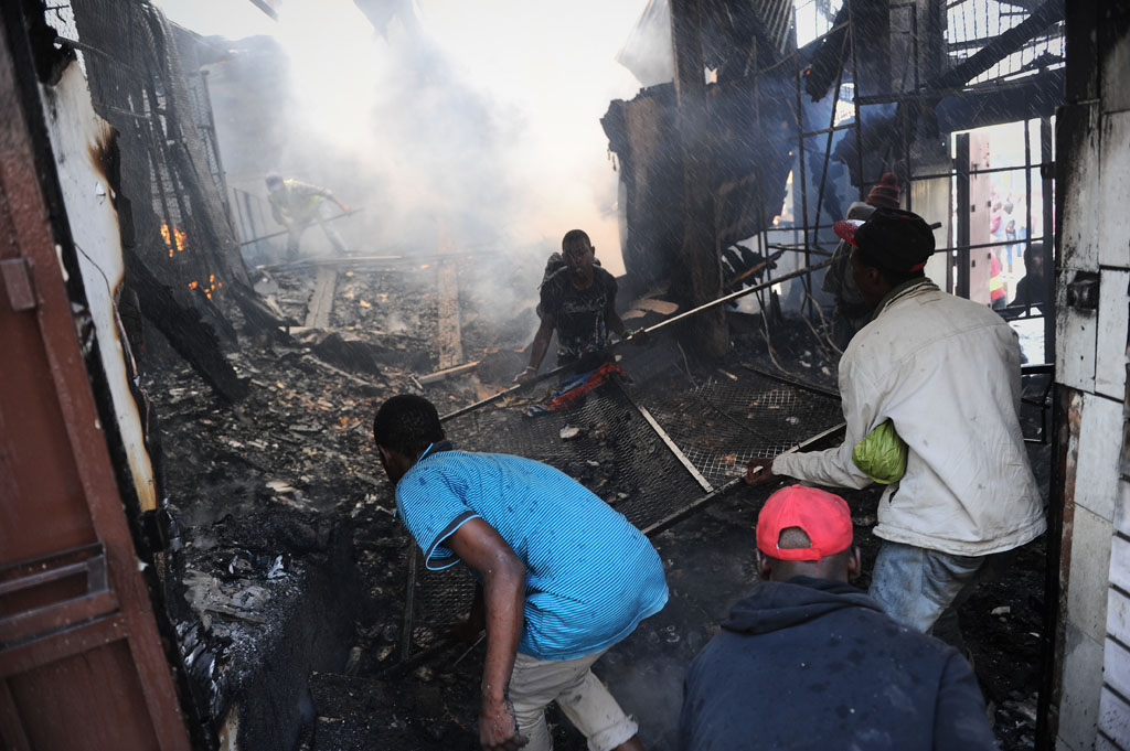 Scrap metal scavengers salvage what they can from a burning building as firefighters attempt to extinguish a fire at the corner of Albertina Sisulu Road and Troye Street in the Johannesburg CBD, 6 March 2018. While attempting to extinguish the blaze, the Emergency Management Services had to contend with groups of people attempting to loot the building of whatever scrap metal they could find. Firefighters resorted to blasting the scavengers with their water hoses. A handful of JMPD officers attempted to keep the large crowds at bay. Picture: Michel Bega