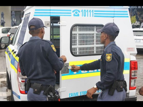 Police officers locking in some of the suspects in a police van.