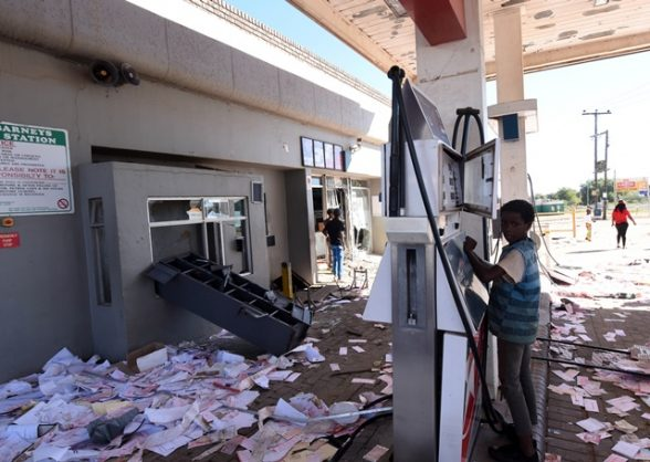 A young boy plays with a petrol pump at Caltex Garage after it was vandalized by Mahikeng residents during service delivery protests, 20 April 2018. Residents demand service delivery and the removal of premier Supra Mahumapelo. Picture: Nigel Sibanda