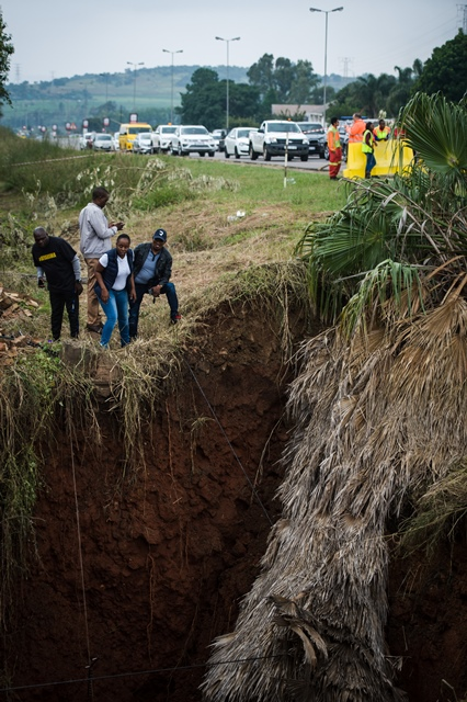 Passers-by are seen looking into a massive sinkhole pictured along the R55 outside Laudium that has been sinking deeper over the easter weekend, 2 April 2018, Pretoria. Picture: Jacques Nelles