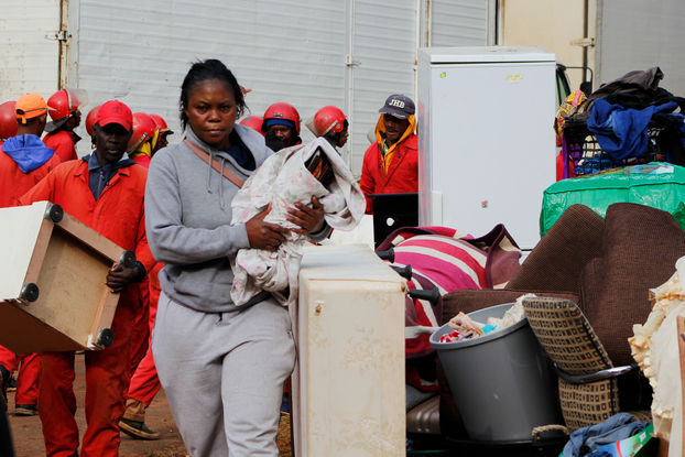 An evicted tenant carries her belongings away from the Red Ants.