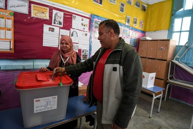 A Tunisian policeman in civilian clothes votes in municipal elections at a polling station in Tunis on April 29, 2018