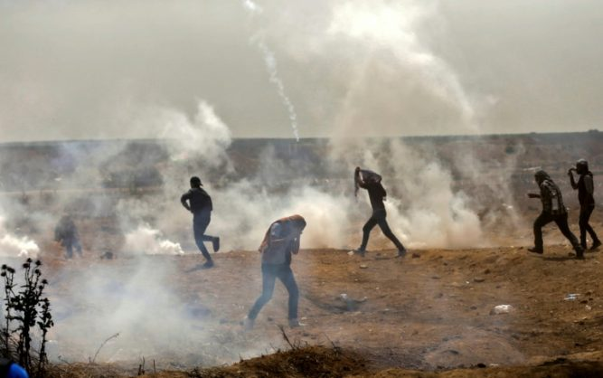 Palestinians take cover from tear gas during clashes with Israeli security forces near the Gaza border fence.