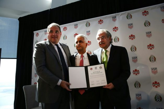 Sunil Gulati, (center) president of the United States Soccer Federation (USSF), Canadian CONCACAF President Victor Montagliani (left) and Mexican Football Federation President Decio De Maria hold up a signed unified bid for the 2026 soccer world cup on April 10, 2017 in New York City