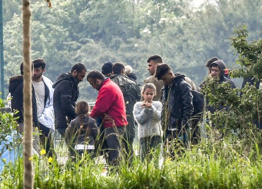 Migrants prepare to board a bus taking them to migrants reception centres of the region on May 24, 2018 in Grande-Synthe, northern France, during an evacuation operation of Kurdish migrants from Iraq, settled near a gymnasium. Picture: AFP Photo / Philippe Huguen.