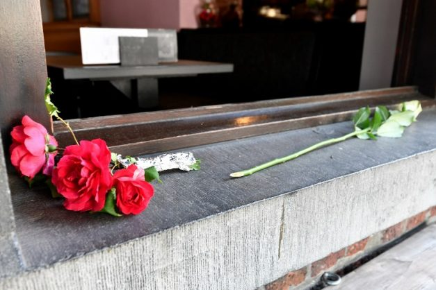Flowers are layed at the cafe Les Augustins, just after the security perimetre was lifted, at the scene of a deadly shooting on the boulevard d'Avroy in the eastern Belgian city of Liege, on May 29, 2018. A gunman on on May 29 shot dead two female police officers with their own weapons before killing a bystander in a brazen suspected terror attack in Belgium, briefly taking a hostage at a school before being killed by police. The carnage in the gritty eastern industrial city of Liege began around 10:30 am (0830 GMT) when the attacker armed with a knife repeatedly stabbed the two officers before using their own firearms to kill them, prosecutors said.   / AFP PHOTO / Belga / ERIC LALMAND / Belgium OUT