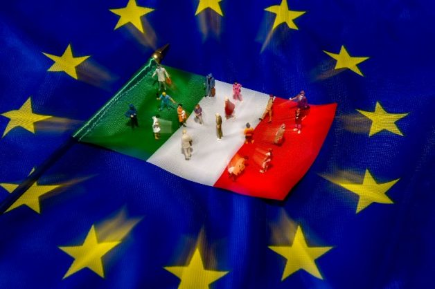 A picture taken on May 30, 2018 shows figurines on an Italian flag lying on a European Union flag. Italy, one of the European Union's biggest economies, has been plunged into crisis after President Sergio Mattarella at the weekend vetoed the new government's nomination of a fierce eurosceptic as economy minister. / AFP PHOTO / PHILIPPE HUGUEN