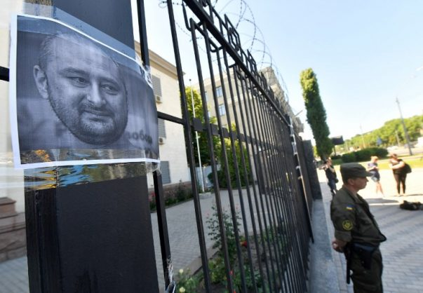 Ukrainian National guard servicemen stand in front of Russian embassy in Kiev, on May 30, 2018, where portraits of journalist Arkadi Babchenko have been hung by activists to the fence one day after he was shot in his apartment building in the Ukrainian capital. / AFP PHOTO / Sergei SUPINSKY