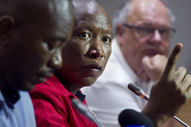 Economic Freedom Fighters (EFF) party leader Julius Malema (2nd L) speaks flanked by Democratic Alliance (DA) party leader Mmusi Maimane (L), United Democratic Movement leader Bantu Holomisa (2nd R) and Corne Mulder (R) of the Freedom Front Plus (FF+), as they give a press conference.  / AFP PHOTO / RODGER BOSCH