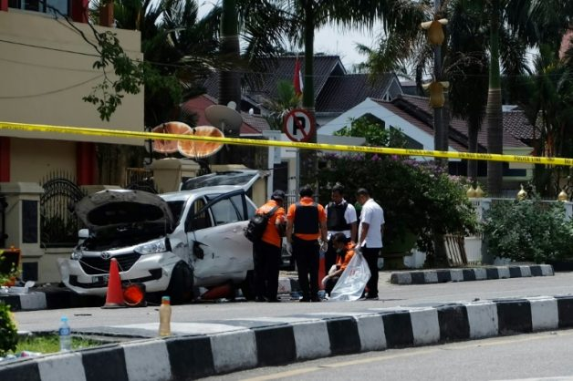 Indonesian policemen examine a car used by attackers during an assault on a police headquarters on the island of Sumatra that left one officer dead and two wounded | © AFP | DEDY SUTISNA