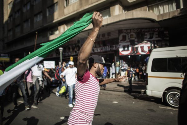 FILE PICTURE: A man runs holding a Nigerian flag as thousands marched against xenophobic attacks in South Africa AFP PHOTO/GIANLUIGI GUERCIA