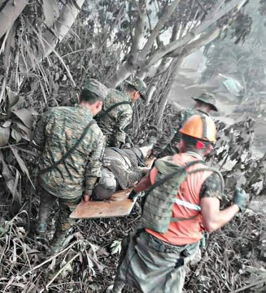This handout picture released by the Guatemalan National Army shows army personnel as they evacuate a victim of Guatemala's Volcano Fuego eruption in El Rodeo, Guatemala on June 3, 2018.  At least six people were killed when Guatemala's Fuego volcano erupted, belching ash and rock and forcing the airport to close. The strong eruption was the second major one this year. The dead were from farming communities just south of the volcano who were trapped by hot lava flow, National Disaster Relief Agency spokesman David de Leon told reporters / AFP PHOTO / AFP PHOTO AND Guatemala National Army / HO / RESTRICTED TO EDITORIAL USE  - NO MARKETING NO ADVERTISING CAMPAIGNS - DISTRIBUTED AS A SERVICE TO CLIENTS