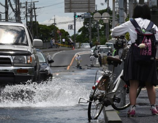 Cars and a student with a bicycle pass a flooded road following an earthquake in Takatsuki, north of Osaka prefecture on June 18, 2018. At least two people, including a child, were killed on June 18, after a strong quake rocked the second city of Osaka during the morning rush hour, Japan's government said. / AFP PHOTO / JIJI PRESS / STR / Japan OUT