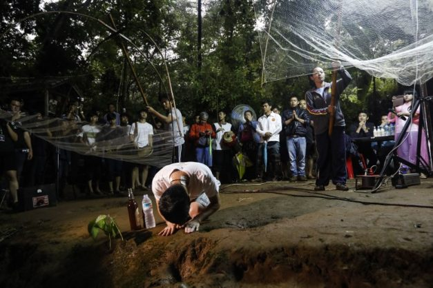 Family members and relatives pray at the entrance of Tham Luang cave while rescue personnel conduct operations to find the missing members of the children's football team along with their coach at the cave in Khun Nam Nang Non Forest Park in Chiang Rai province on June 26, 2018. / AFP PHOTO / THAI NEWS PIX AND AFP PHOTO / Krit Phromsakla Na SAKOLNAKORN