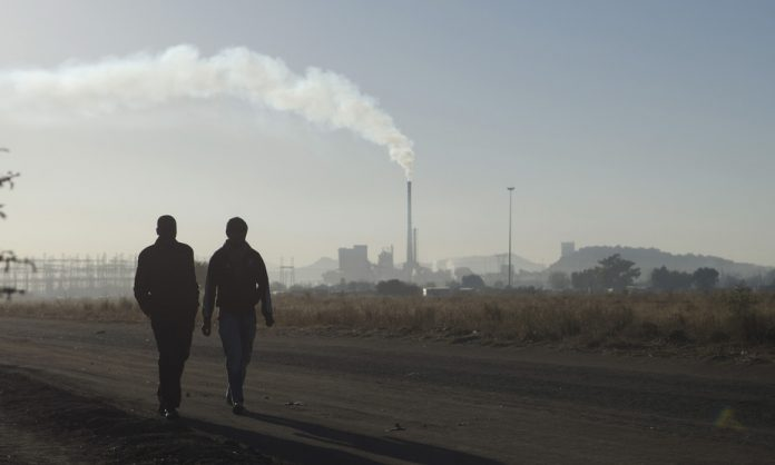 Workers walk past a Lonmin Marikana platinum mine, a site that represents industrial strife in South Africa. Picture: Reuters/Skyler Reid