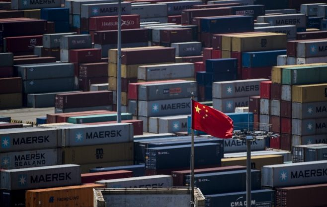 This file picture taken on April 9, 2018 shows a Chinese flag in front of containers at the Yangshan Deep-Water Port, an automated cargo wharf, in Shanghai. Simmering trade tensions between the world's top two economies are set to erupt into a full-blown trade war on July 6, 2018, with Washington poised to impose new tariffs on 34 billion USD in Chinese goods.  Picture: AFP Photo / Johannes Eisele.