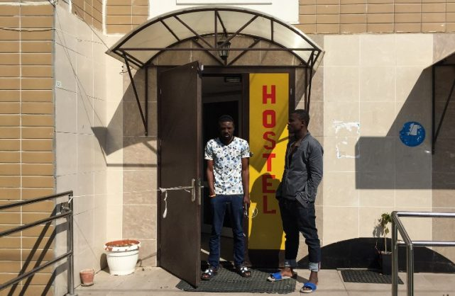 A 25-year-old Nigerian Sodiq Olamilekan (L) stands next to his 21-year-old brother Ismail at a door of a hostel in Moscow on July 12, 2018. Fraudsters have tricked scores of Nigerians by selling them football World Cup fan passes to travel to Russia, leaving many stranded and penniless, victims and anti-trafficking campaigners say. / AFP PHOTO / Roland LLOYD PARRY