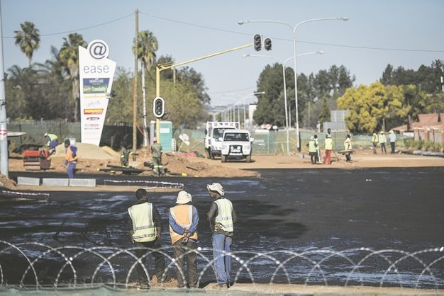 Construction site workers are seen by what was a giant sinkhole on Jean Avenue in Centurion but has recently been repaired, 23 July 2018, Pretoria. Picture: Jacques Nelles