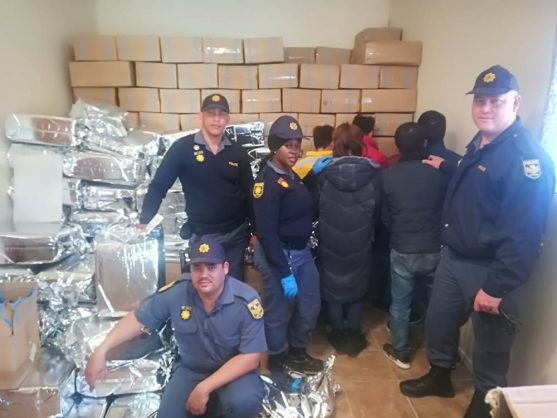 Police with the suspects arrested at the counterfeit-goods factory, as well as manufactured branded merchandise. Picture: ANA