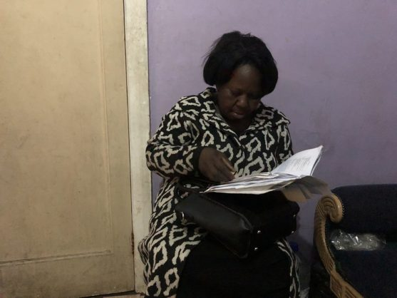 Kundji Tembo goes through her hospital and Home Affairs documents in a room she is sharing with her daughter and two other family members. Photo: Tariro Washinyira