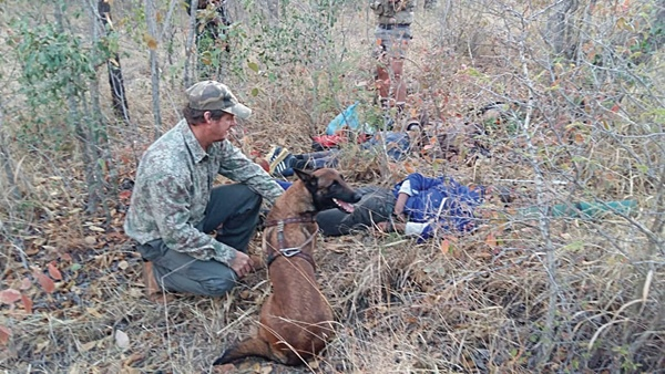 The Endangered Wildlife Trust's antipoaching dog Annie with her handler, Colin, and two of the three poaching suspects she tracked down in the Kruger National Park this week. Picture: Supplied