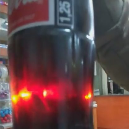 Something appears to be floating inside a sealed bottle of what appears to be a coke bottle.