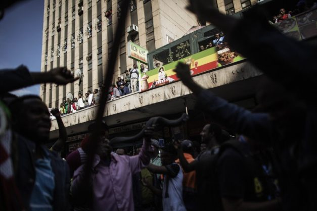 FILE PICTURE: Foreign Nationals cheer from their residences and shops as thousands march against the recent wave of xenophobic attacks in South Africa through the streets of Johannesburg CBD on April 23, 2015.