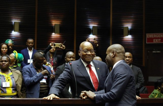 Former South African president Jacob Zuma (L) speaks with his lawyer Daniel Mantsha at the High Court of Pietermaritzburg on July 27, 2018 before his hearing over 16 corruption charges. He is charged with 16 counts that include fraud' corruption and racketeering. These charges relate to 783 payments which he allegedly received as a bribe to protect French arms company' Thales from an investigation into the controversial multi-billion rand arms deal. The alleged bribe was facilitated by Zuma's former financial adviser' Schabir Shaik. / AFP PHOTO / POOL / Phill MAGAKOE