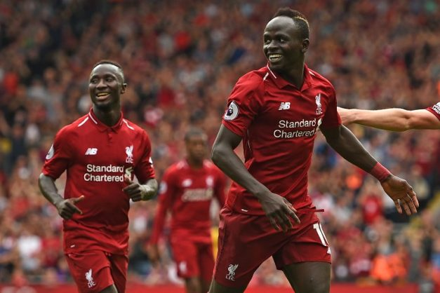 Liverpool's Senegalese striker Sadio Mané (R) celebrates after scoring their third goal during the English Premier League football match between Liverpool and West Ham United at Anfield in Liverpool, north west England on August 12, 2018. / AFP PHOTO / Oli SCARFF / RESTRICTED TO EDITORIAL USE. No use with unauthorized audio, video, data, fixture lists, club/league logos or 'live' services. Online in-match use limited to 120 images. An additional 40 images may be used in extra time. No video emulation. Social media in-match use limited to 120 images. An additional 40 images may be used in extra time. No use in betting publications, games or single club/league/player publications. /