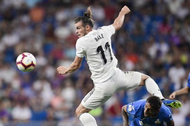 Real Madrid's Welsh forward Gareth Bale (L) challenges Getafe's Uruguayan defender Damian Suarez during the Spanish League football match between Real Madrid and Getafe at the Santiago Bernabeu stadium in Madrid on August 19, 2018. / AFP PHOTO / JAVIER SORIANO