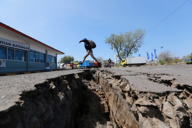 A man jumps over a crack in the ground in Mataram on Indonesia's Lombok island on August 20, 2018 after a series of earthquakes were recorded by seismologists throughout August 19. A series of powerful earthquakes have rocked the Indonesian holiday island of Lombok, killing at least 10 people and setting off fresh waves of panic after nearly 500 died there following a huge tremor two weeks ago. Picture: AFP PHOTO.