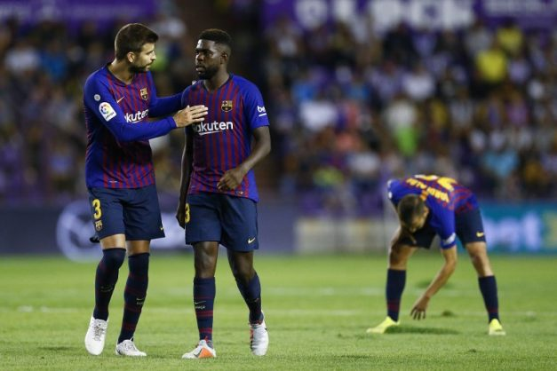 Barcelona's Spanish defender Gerard Pique (L) talks to Barcelona's French defender Samuel Umtiti during the Spanish league football match between Real Valladolid and FC Barcelona at the Jose Zorrilla Stadium in Valladolid on August 25, 2018. / AFP PHOTO / Benjamin CREMEL